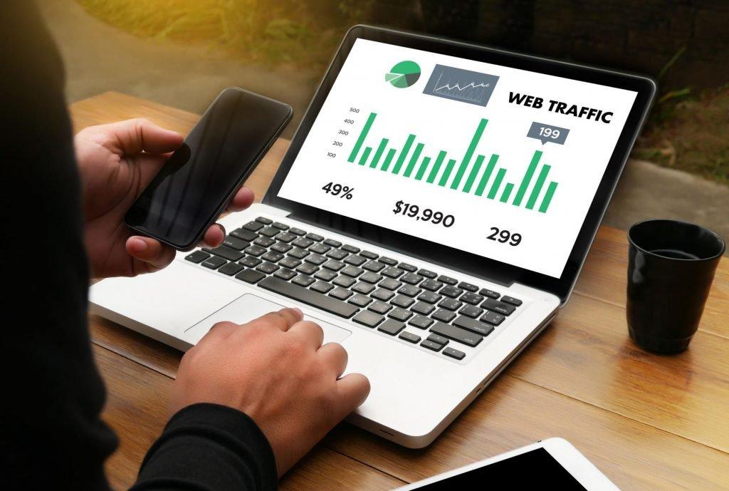profissional acessando laptop com dados de tráfico pago de web